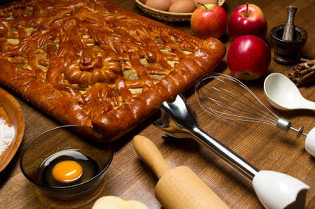 Apple pie with baking ingredients, spices and kitchen tools for cooking, rustic homemade sweet food on a wooden table, selective focus