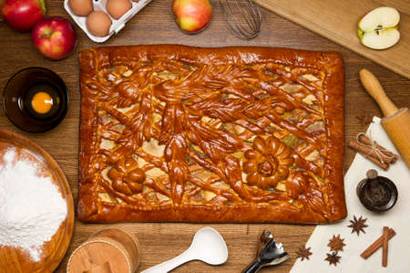 Apple pie with baking ingredients, spices and kitchen tools for cooking, rustic homemade sweet food on a wooden table, top view