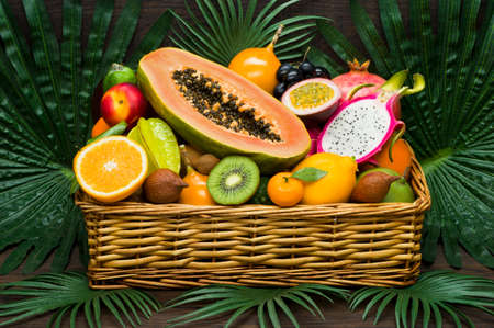 Fresh Thai fruits in wicker basket on palm leaves and wooden background, healthy food, diet nutrition