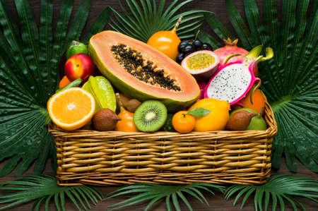 Verse Thaise vruchten in rieten mand op palmbladen en houten achtergrond, gezond voedsel, dieetvoeding Stockfoto