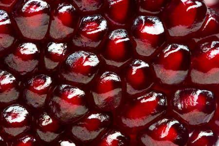 Pomegranate background, half of fresh juicy red garnet fruit, natural abstract texture, macro shot