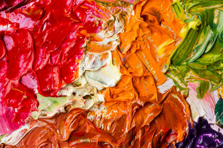 Artists palette with mixed oil paints, macro, colorful stroke texture on canvas, studio shot, abstract art background