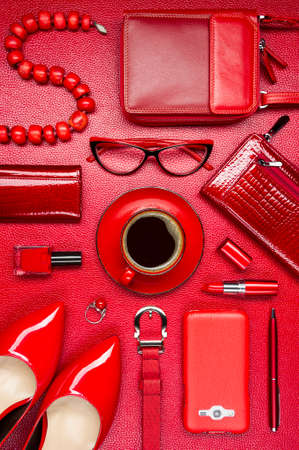 Red woman accessories, coffee, cosmetic, jewelry, shoes, gadget and other luxury objects on a leather background, fashion industry, modern female concept Standard-Bild