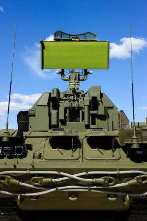 Air defense radar of military mobile antiaircraft system in green color, modern army industry, blue sky and white clouds on background
