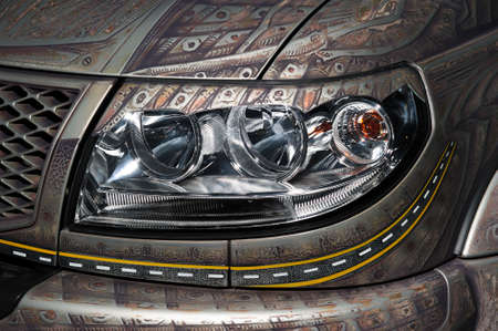 Car headlight with led and xenon lamps of modern powerful offroader vehicle with pattern on gray bodywork
