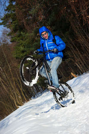 Extreme cyclist standing on rear wheel of his mountain bike, winter sport, cross country biking on snowy road