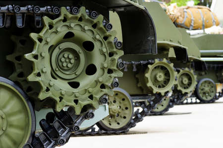 Tank tracks and steel wheels of heavy armored vehicles with green bodywork in row, military industry, modern army equipment, selective focus Stok Fotoğraf