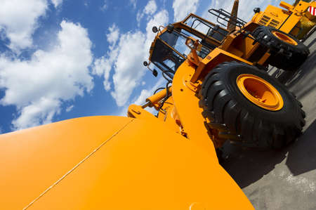 Wheel loader, orange construction machine with big scoop and black wheels, heavy industry, blue sky and white clouds on background