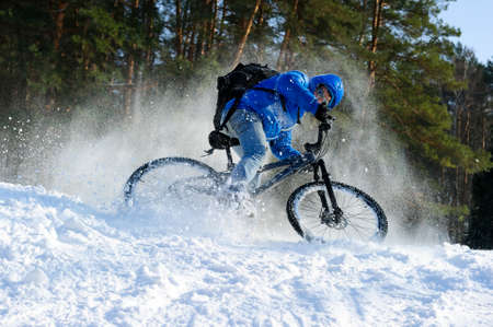 Extreme cyclist riding bicycle surrounded by snow, winter sport, cross country biking near forest in cool sunny day Standard-Bild - 119608988