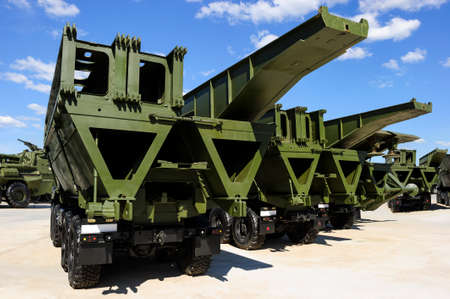 Military mechanized bridges in row, army engineering equipment, heavy industry, white clouds and blue sky on background Standard-Bild - 119608999