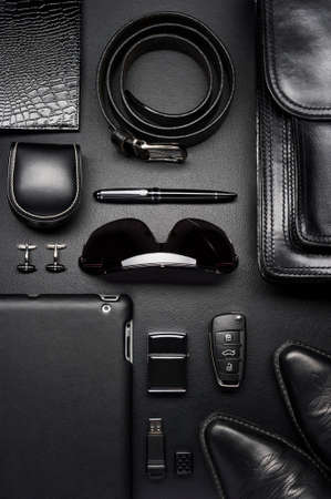 Man accessories in business style, briefcase, gadgets, shoes, clothes and other luxury businessman attributes on leather black background, fashion industry, top view Standard-Bild - 119609004