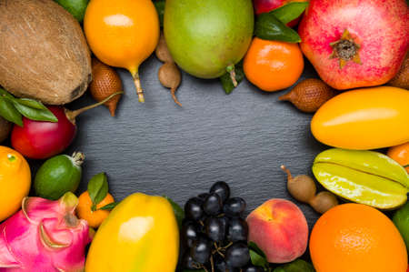 Exotic tropical fruits on black textured stone background, healthy food, vegetarian diet Standard-Bild - 119609012