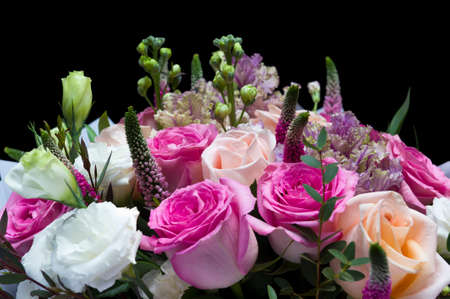 Flower bouquet, bunch of pink and peach roses, white lisianthus, red veronica spicata or garden speedwell and green eucalyptus isolated on black background, springtime concept, selective focus