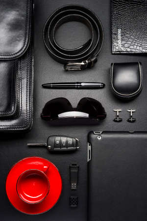 Man accessories in business style with empty red coffee cup, gadgets, car key, cufflinks, sunglasses, briefcase and other luxury businessman attributes on leather black background, fashion industry Standard-Bild - 119609018