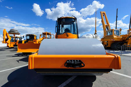 Steamroller for road works, bulldozer, tractor, loader, crane and other construction machines, heavy industry, blue sky and white clouds on background