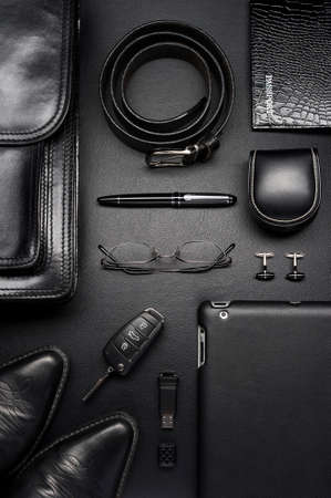 Mann-Accessoires im Business-Stil, Aktentasche, Gadgets, Schuhe, Kleidung und andere Luxus-Geschäftsmann-Attribute auf schwarzem Lederhintergrund, Modeindustrie, Draufsicht