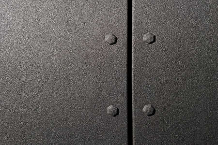 Surface of powerful suv bodywork, side part of car with bolts and black textured paint coating, detail of vehicle