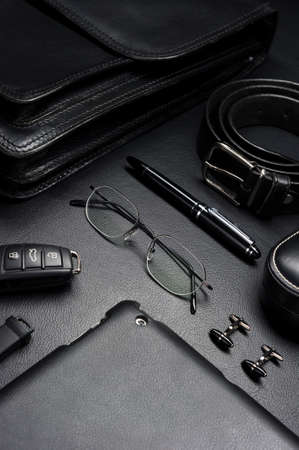 Man accessories in business style, gadgets, eyeglasses, car key, briefcase and other luxury objects on leather black background, fashion industry, selective focus Stok Fotoğraf