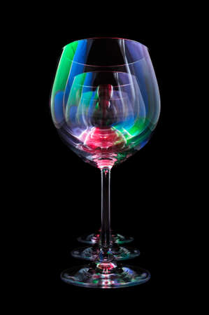 Party wine glasses lit by red, green, blue nightclub lights, nightlife and entertainment industry, objects in row isolated on black background