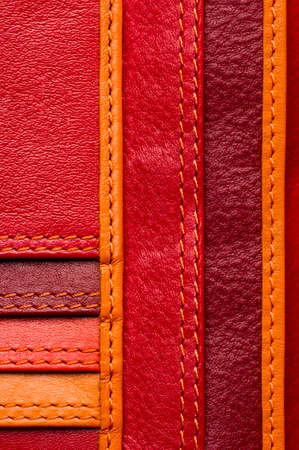Leather samples with stitches, natural materials with seams of red, maroon, brown, orange colors and other warm shades, woman bag detail, macro shot, selective focus Reklamní fotografie