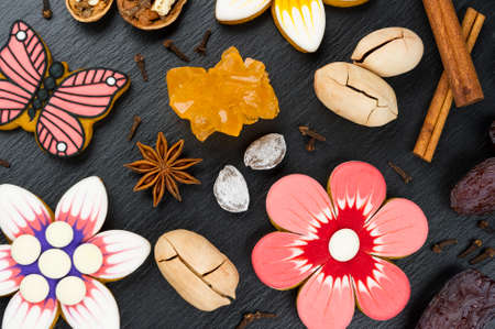 Gingerbread cookies with nuts, dates and spices, colorful homemade cakes in shape of flower and butterfly on black textured background, top view Stock fotó