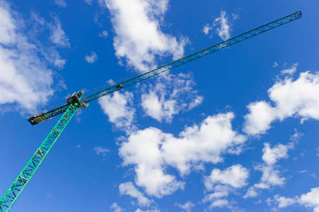 Green construction tower crane, heavy industry, blue sky and white clouds on background, bottom view