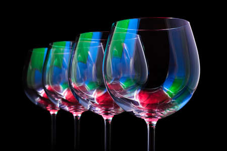 Nightclub wine glasses lit by red, green, blue party lights, nightlife and entertainment industry, four object in row isolated on black background Stock fotó