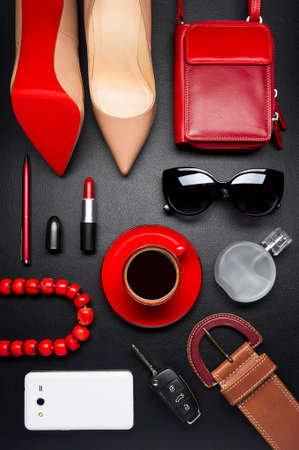 Woman accessories, clothing, jewelry, gadget, cosmetics in red color and cup of coffee on leather black background, lifestyle, modern female concept, fashion industry