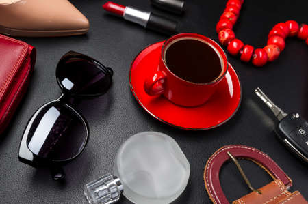 Woman accessories, clothing, jewelry, cosmetics in red color and cup of coffee on leather black background, lifestyle, modern female concept, fashion industry