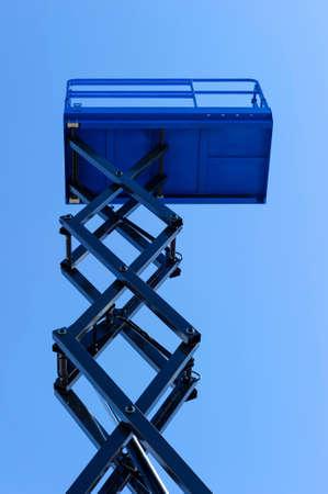 Scissor lift platform with bucket, construction machine, heavy industry, blue sky on background, bottom view