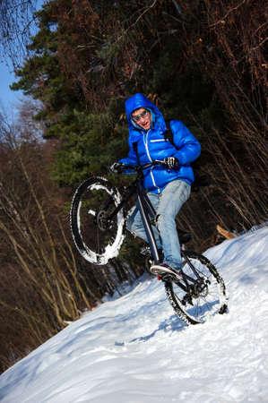 Cycliste extrême debout sur la roue arrière de son vélo de montagne, sport d'hiver, vélo de fond sur une route enneigée près de la forêt par une journée fraîche et ensoleillée
