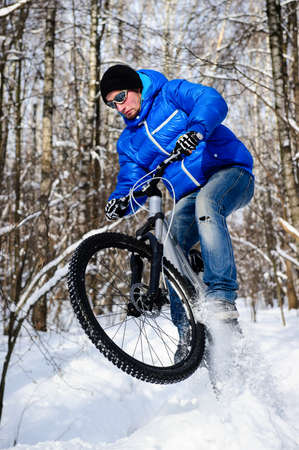 Cyclist on mountain bicycle, extreme cycling in winter forest in sunny cold day
