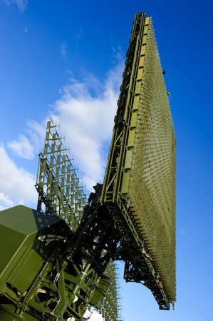 Air defense radars of military mobile antiaircraft system in green color, modern army industry, blue sky and white clouds on background