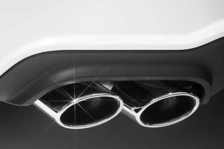 Double chrome exhaust pipe of sport car with white bodywork and plastic bumper, automobile industry, selective focus, monochrome shot Zdjęcie Seryjne