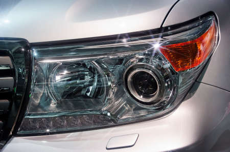 Car headlight with led and xenon lamps of modern powerful offroader vehicle with silver gray bodywork, automobile industry