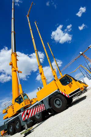 Mobile construction cranes with telescopic arms mounted on trucks with yellow bodyworks, other cranes, white clouds and deep blue sky on background, heavy industry Zdjęcie Seryjne