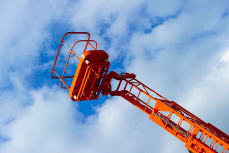 Hydraulic lift platform with bucket of construction vehicle painted in orange color with white clouds and blue sky on background, heavy industry