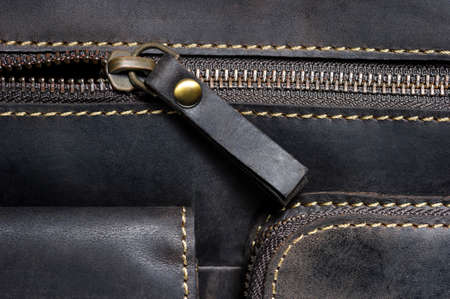 Leather bag with zipper, pockets and stitches, man accessories in vintage style, fashion industry, macro shot