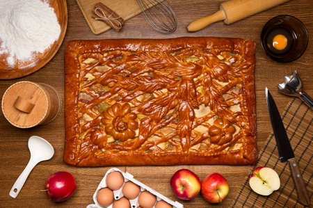 Apple pie with baking ingredients, spices and kitchen tools for cooking, rustic homemade sweet food on wooden table, top view Zdjęcie Seryjne