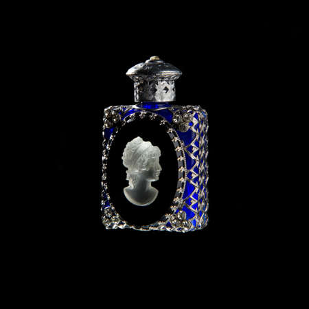 Vintage perfume bottle of blue glass and silver with bas-relief profile women of stone isolated on black background Standard-Bild