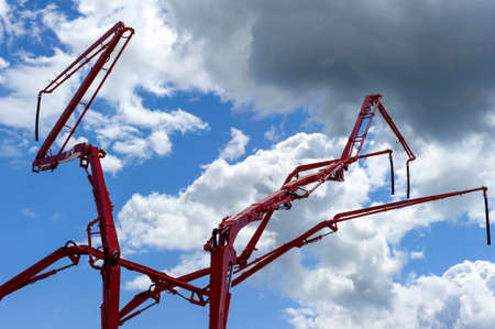 Construction cranes with concrete pumps, heavy industry, blue sky and white clouds on background Standard-Bild