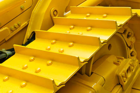 Bulldozer tracks and drive gear with sprocket mechanism, large construction machine with bolts and yellow paint coating, heavy industry, detail Standard-Bild