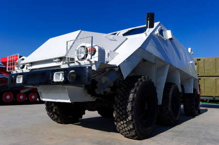Armored personnel carrier or APC, white military wheeled all-terrain bulletproof vehicle, army industry, other military machines and blue sky on background