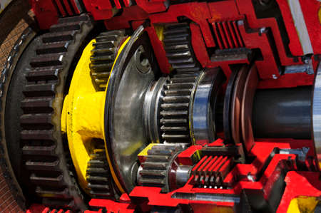 Bulldozer drive gear mechanism cross section, sprockets, bearings of diesel engine, large construction machine of red and yellow colors, heavy industry Standard-Bild