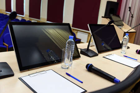 Conference room for business meeting, table with microphones, monitors, bottles with water, glasses, papers, pens and chairs, blue seats in row on blurred background, selective focus