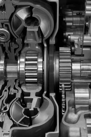 Gear box cross section, engine industry, sprockets, cogwheels and bearings of automotive transmission for oversize trucks and construction vehicles, selective focus, monochrome shot
