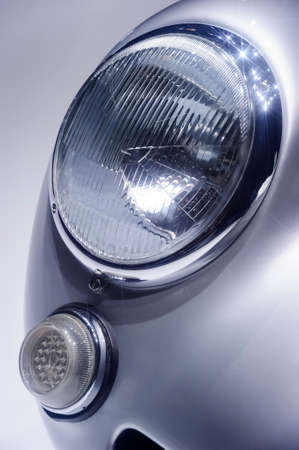 Retro car headlight with chrome parts on hood, vintage vehicle with silver bodywork, classic sedan, automobile industry 写真素材
