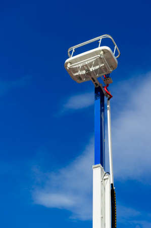 Hydraulic lift platform with bucket, construction industry, blue sky and white clouds on background