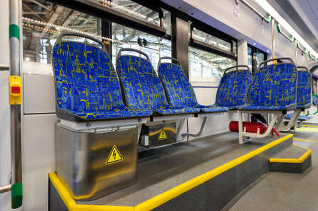 Tram inside, city transportation interior with blue seats in row, chrome handles for standing passengers, bright lights and air conditioner