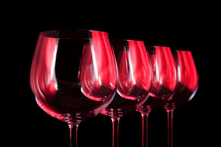 Nightclub wine glasses lit by red party lights, nightlife and entertainment industry, four object in row isolated on black background Standard-Bild